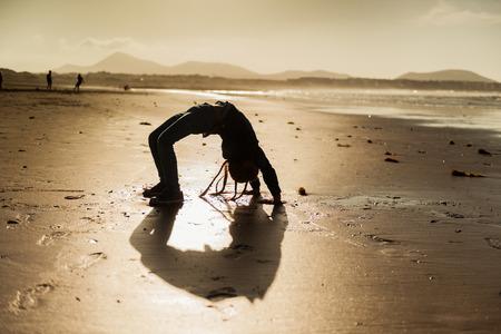 gymnastik: Kleiner Gymnast silhouette am Strand bei Sonnenuntergang Lizenzfreie Bilder