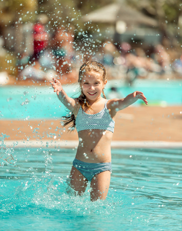 water play: happy little girl in the pool