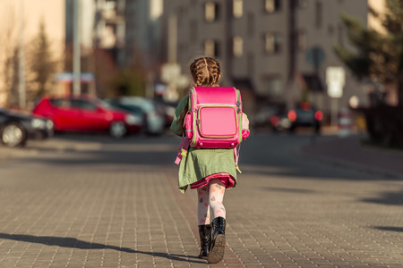 in the back: little  girl with a backpack going to school