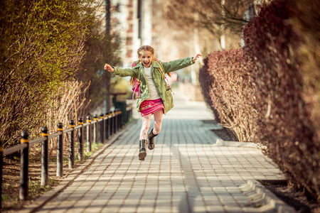 smiles: happy little girl running home from school Stock Photo