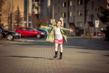 8 9 years: happy little girl running home from school Stock Photo