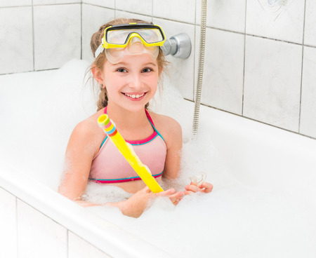 little girl bath: girl in sunglasses dive with the tube in the bath with foam