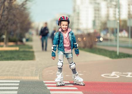 rollerskater: little cute girl riding on roller skates on the bike path