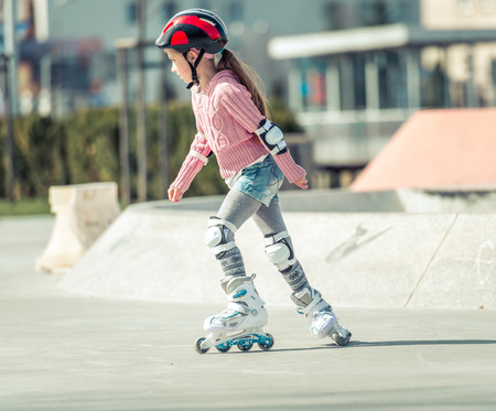 Little pretty girl on roller skates in helmet at a park