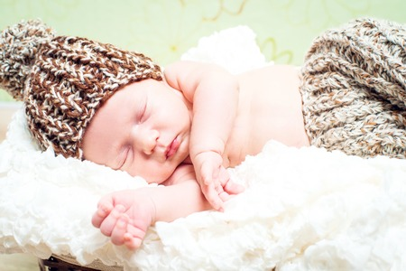 0 3 months: newborn boy in pants and hat asleep in the basket Stock Photo
