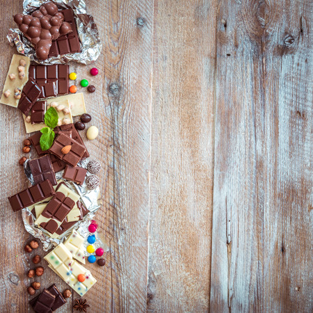 chocolate and candies on a wooden background with space for text photo