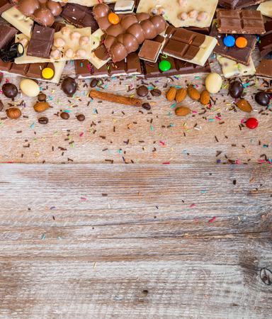 チョコレートやテキストのためのスペースを持つ木製の背景にキャンディー