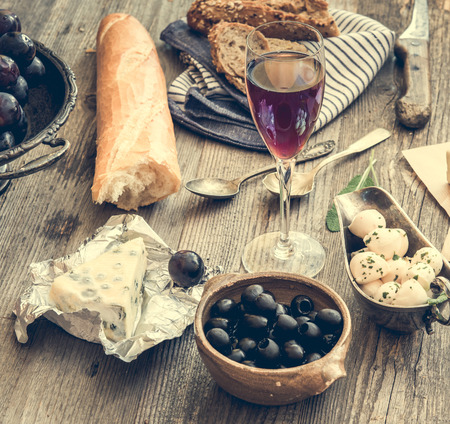pan y vino: Cocina francés. Diferentes tipos de queso, el vino y otros ingredientes en una mesa de madera