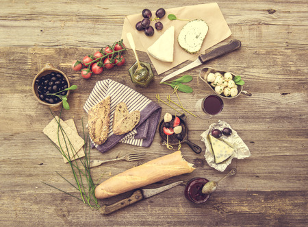 different types of cheese: French snacks on a wooden background. Different types of cheese, wine and other ingredients on a wooden table