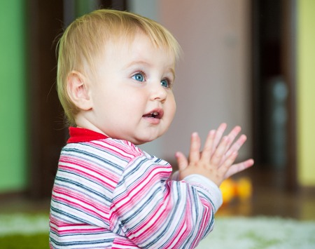 baby blue: cute blue-eyed toddler in the nursery close-up claps Stock Photo