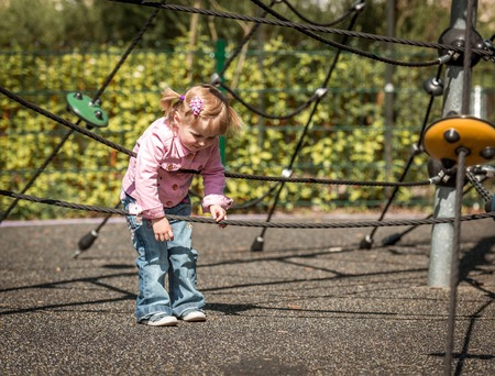 2 persons only: Cute little girl on outdoor playground equipment