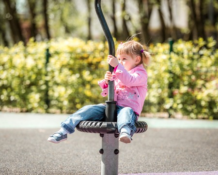 3 persons only: Cute little girl on outdoor playground equipment