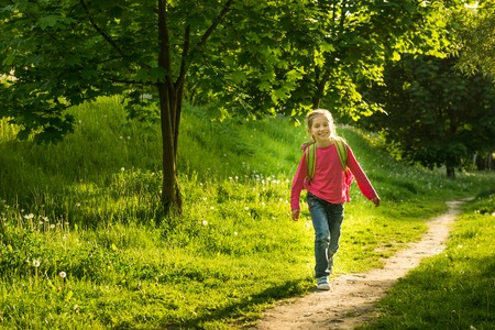 8   9 years: happy little girl go to school through the forest