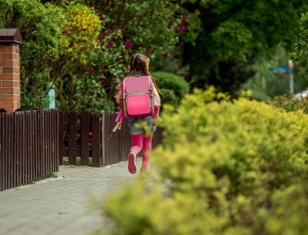 8   9 years: little girl with a backpack run  to school. back view Stock Photo