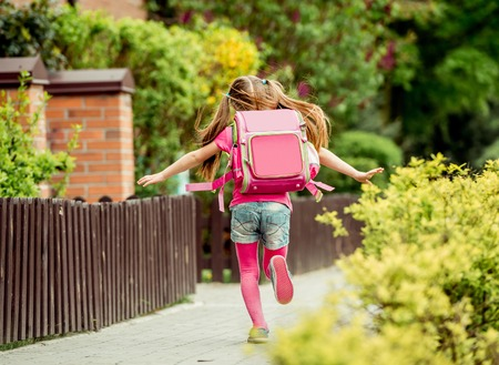 kleines Mädchen mit einem Rucksack in die Schule laufen. Rückansicht
