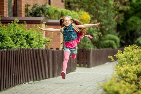 kleines Mädchen mit einem Rucksack von der Schule laufen