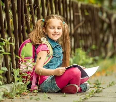 Little mooie schoolmeisje lezen van een boek zittend op de straat Stockfoto - 40854476