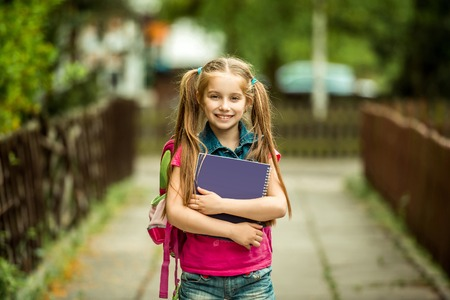 Little pretty schoolgirl with the book on the street