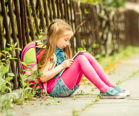 personas de espalda: La peque�a colegiala leyendo un libro sentado en la calle