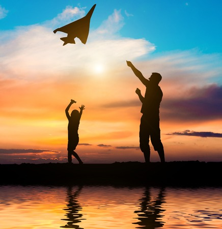 Dad and daughter flying a kite on the beach. silhouette photo