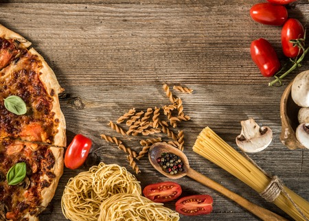 pasta sauce: Italian food background with pizza, raw pasta and vegetables on wooden table