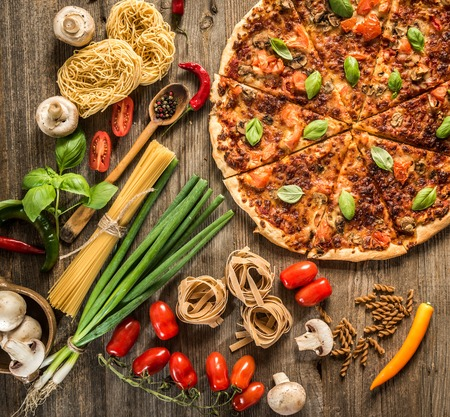 ピザ、生パスタ、木製のテーブルの上の野菜とイタリア料理の背景 写真素材