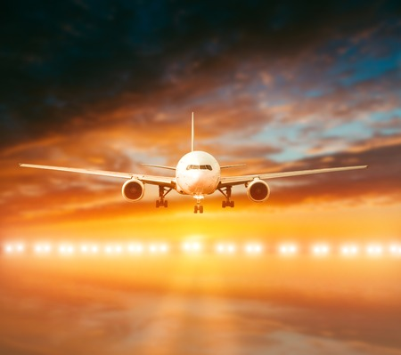 airbus: plane lands on the runway on a background of a magnificent sunset