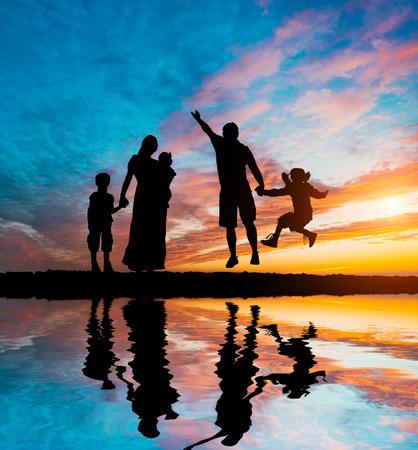 pareja de esposos: happy parents having good time with their little children on the seacoast
