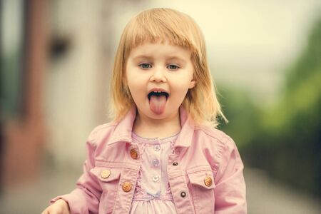 2 year old: Beautiful 2 year old girl showing tongue  in the street close up Stock Photo