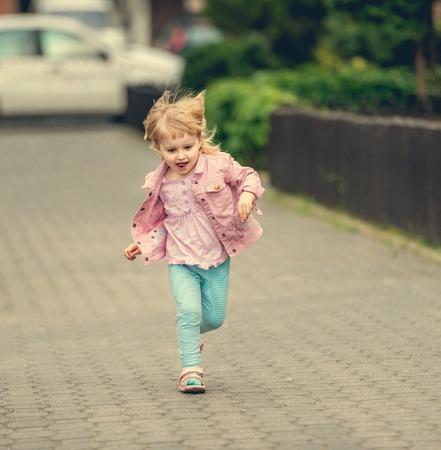 niño corriendo: linda niña corriendo la calle Foto de archivo