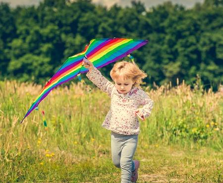 papalote: niña linda que vuela una cometa en un prado en un día soleado. de cerca Foto de archivo