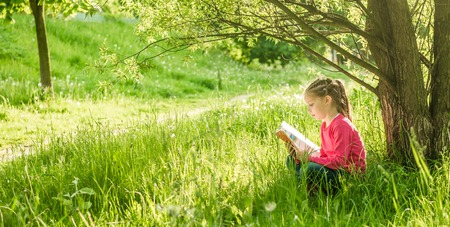 under tree: Cute little girl read the book under tree Stock Photo