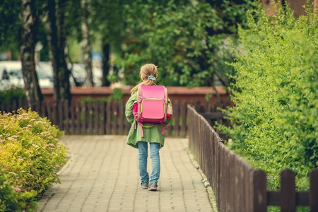 view girl: little girl with a backpack going to school. back view