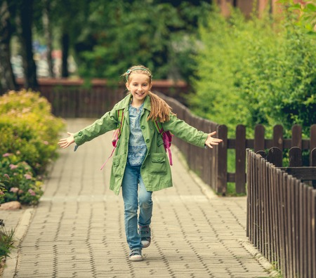 backpacks: happy cute little girl go home from school Stock Photo