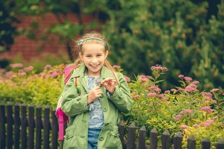 colegiala: pequeña colegiala linda con un morral de la escuela en el fondo de las flores en la calle Foto de archivo