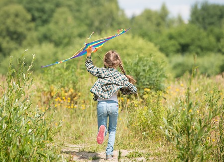 old girl: little cute girl flying a rainbow kite in a meadow on a sunny day. back view
