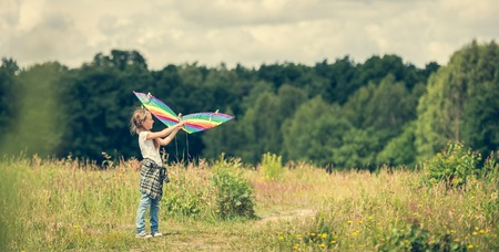 people   lifestyle: little cute girl flying a rainbow kite in a meadow on a sunny day