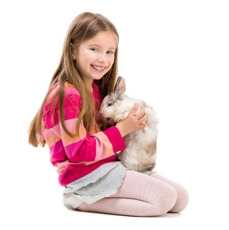 mignonne petite fille: mignonne petite fille dans un chandail rouge avec un bébé lapin sur blanc Banque d'images