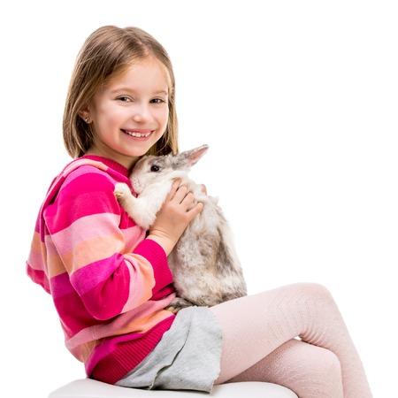 mignonne petite fille: jolie fille dans un chandail pourpre avec un bébé lapin isolé sur fond blanc close-up