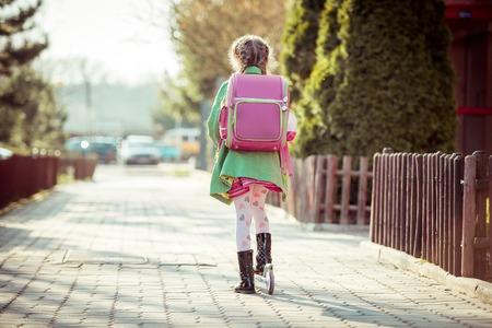 女の子は、スクーターに学校へ行きます。背面図 写真素材