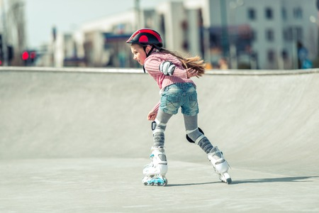 roller: Little pretty girl on roller skates in helmet at a park. back view Stock Photo