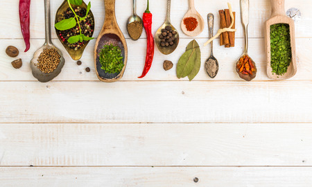 spices: spoons with herbs and spices on white wooden background