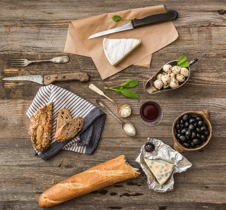 food and wine: French cuisine. Different types of cheese, wine and other ingredients on a wooden table