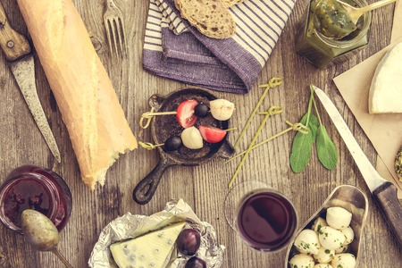 food and wine: French food on a wooden background. Different types of cheese, wine and other ingredients on a wooden table Stock Photo