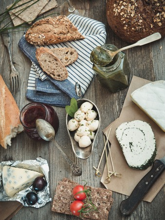 food and wine: Cheese, wine and other food  ingredients on a wooden table. French snacks on a wooden table