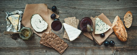 French food on a wooden background. Different types of cheese, wine and other ingredients on a wooden table Stockfoto