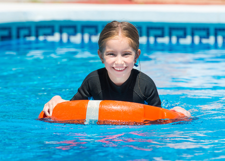 lifeline: happy little girl swims in a wetsuit with a lifeline in the pool in  summer