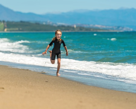 mignonne petite fille: happy cute little girl in a wetsuit running along the coast