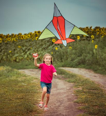 papalote: feliz cometa poco conuna chica en un campo
