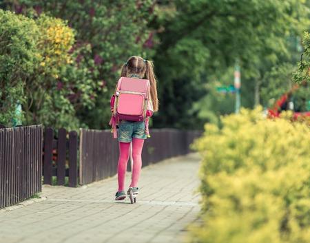 mignonne petite fille: Petite fille avec un sac à dos va à l'école sur un scooter. vue arrière